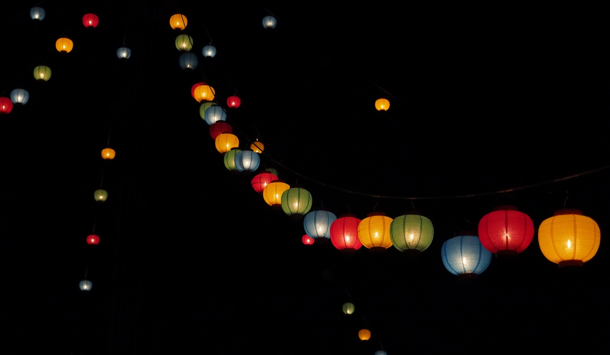 Lanterns hang from a tall tower at night.