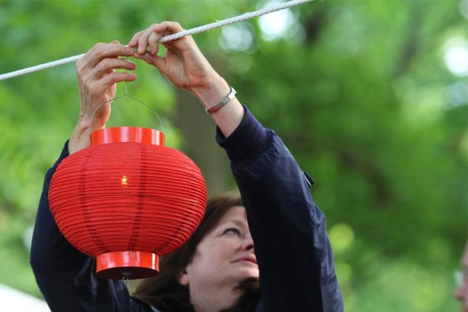 A woman hangs a lantern on a rope