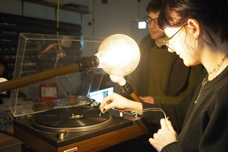A student places a needle on a record with two large light bulbs in front of her.