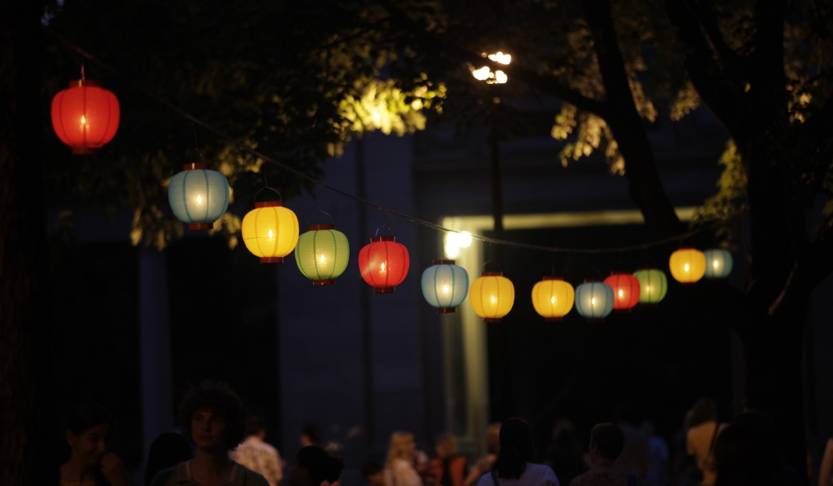 People walk under lanterns at night.