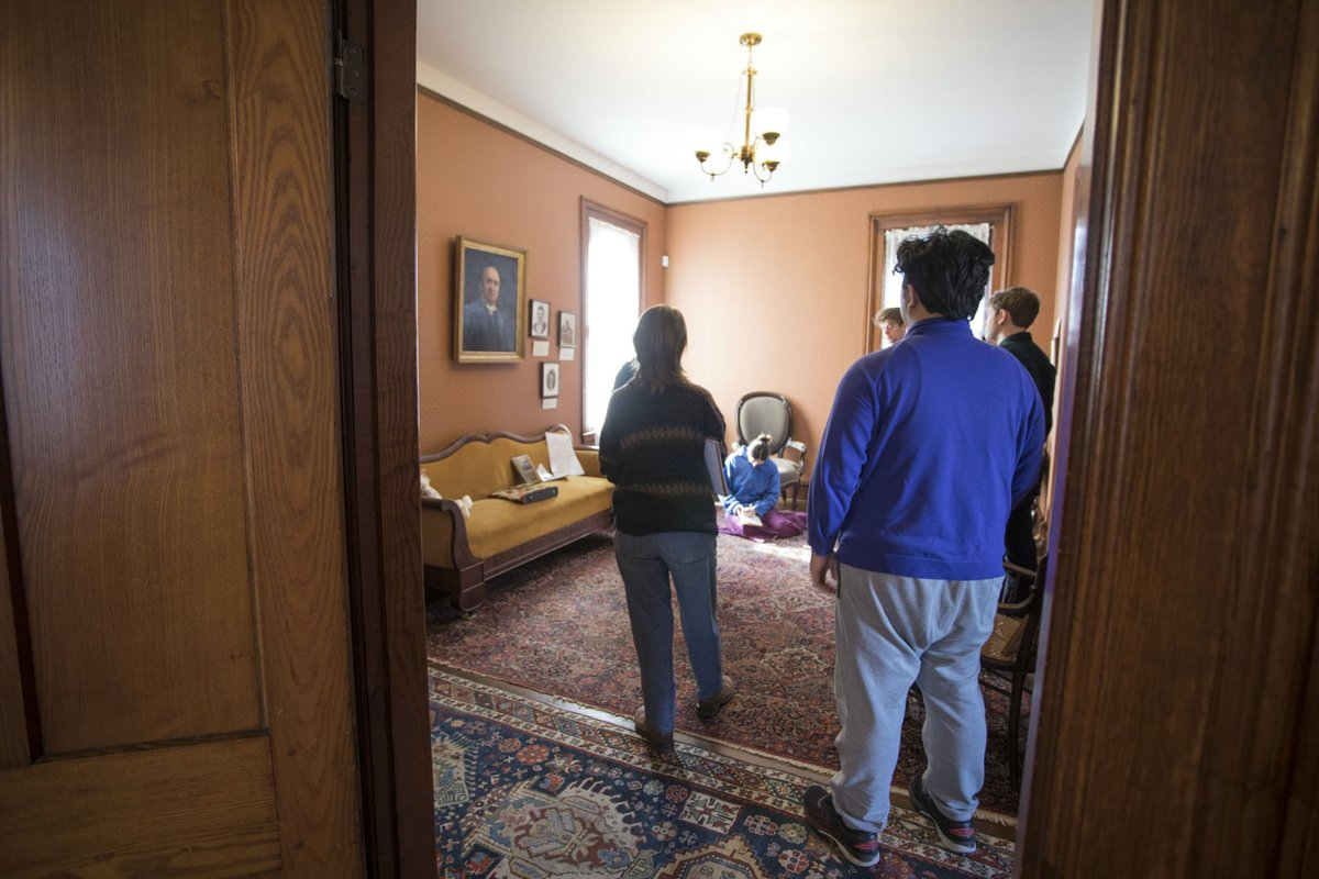A group of students stand in a semi-circle during the tour of a century home.