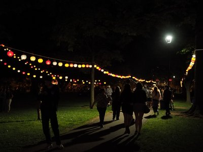 People walking under lanterns in the dark