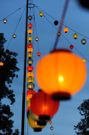 Lanterns hang from a tall tower.