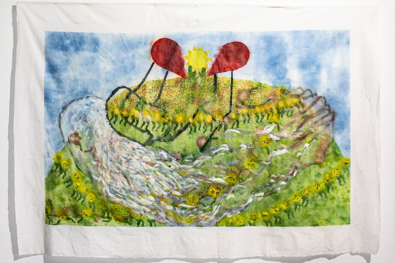 A sheet painted with flowers, hills and a sun.