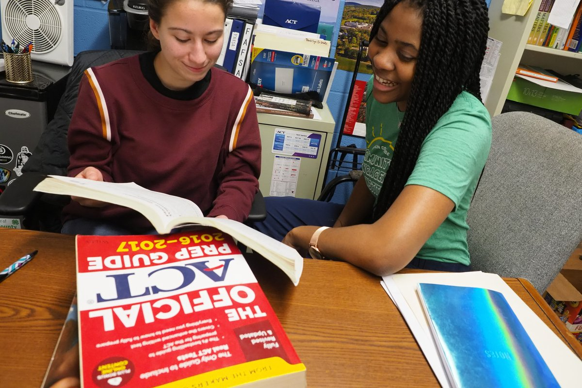 Two students look at a text book together.