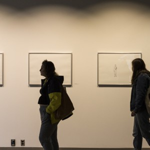 Two students walk by artwork hanging on a wall.