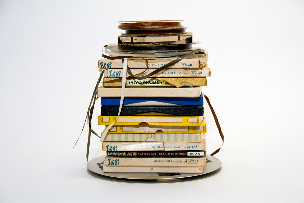A stack of books and CDs with ribbon loosely around it.