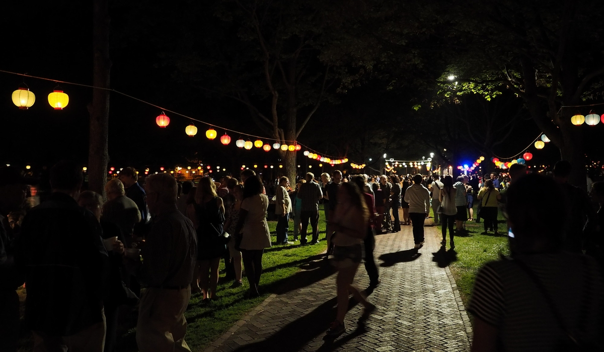 People walk in a park at night with glowing lanterns overhead
