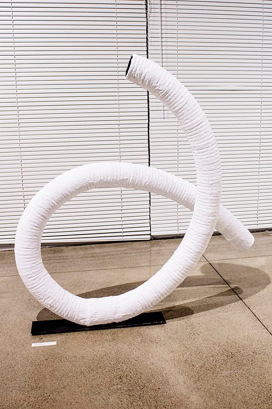 A long large tube sits twisted on a floor.