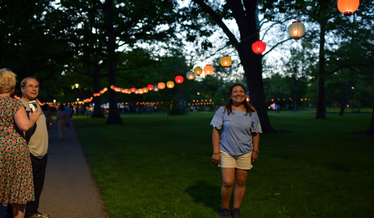 A girl poses for a picture while standing under a lantern