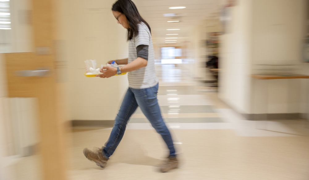 Student walking with a lab tray.