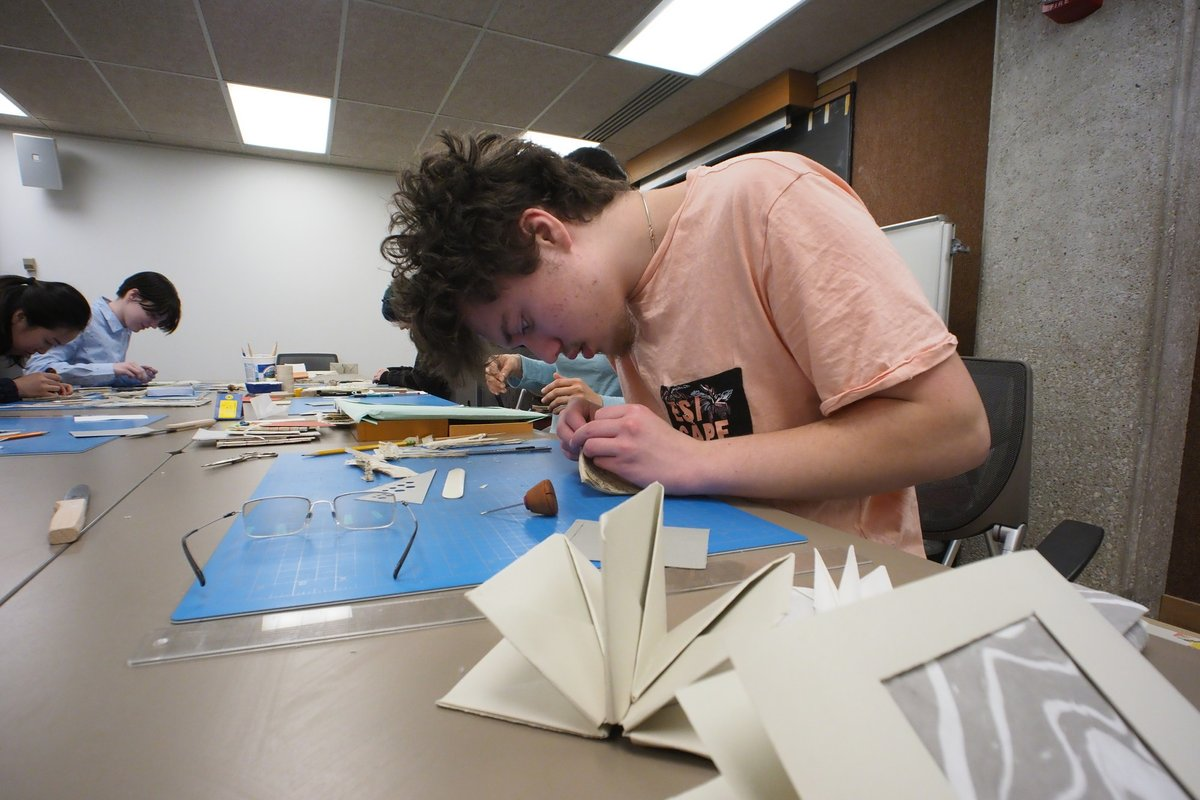 A boy uses instruments to works on a piece of handmade paper.