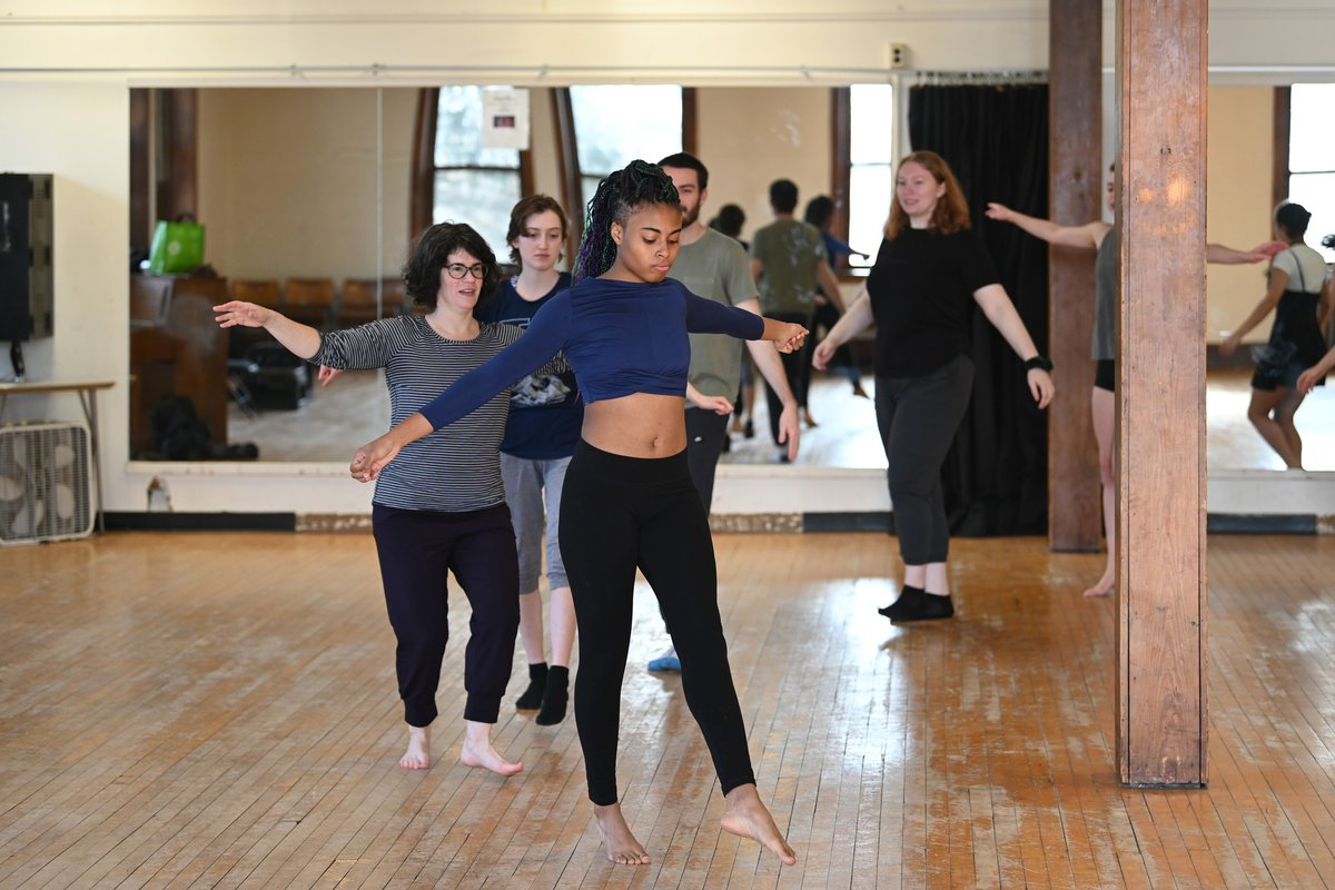 Students dance in a line in a dance studio,