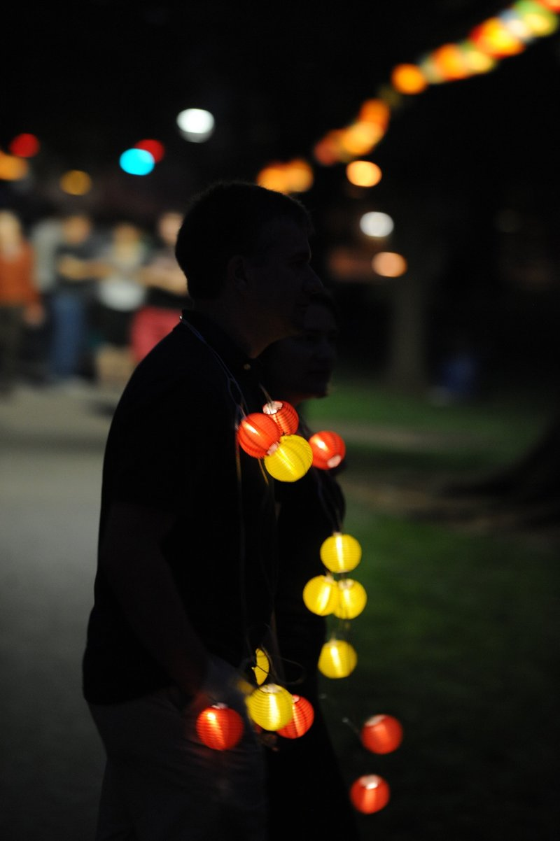 A person wearing a lighted lantern necklace in the dark