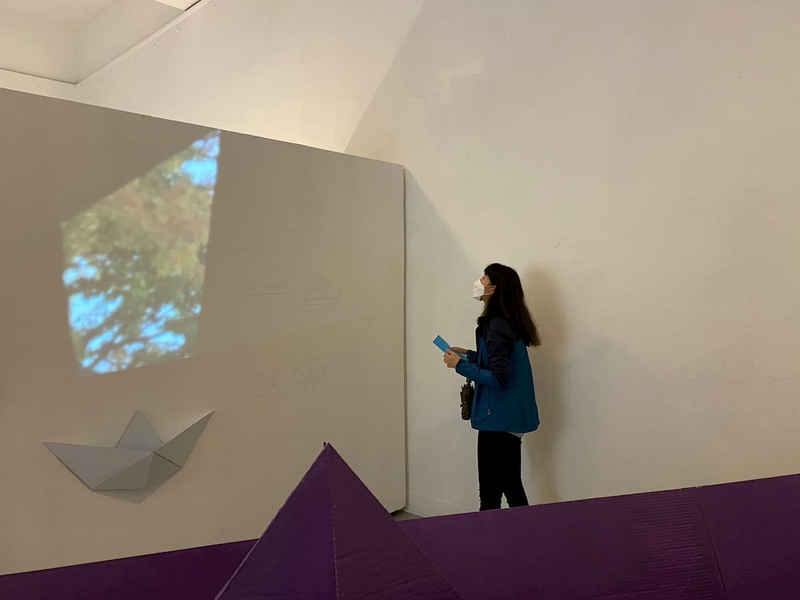 A girl looks up at a projection of an image on a wall.