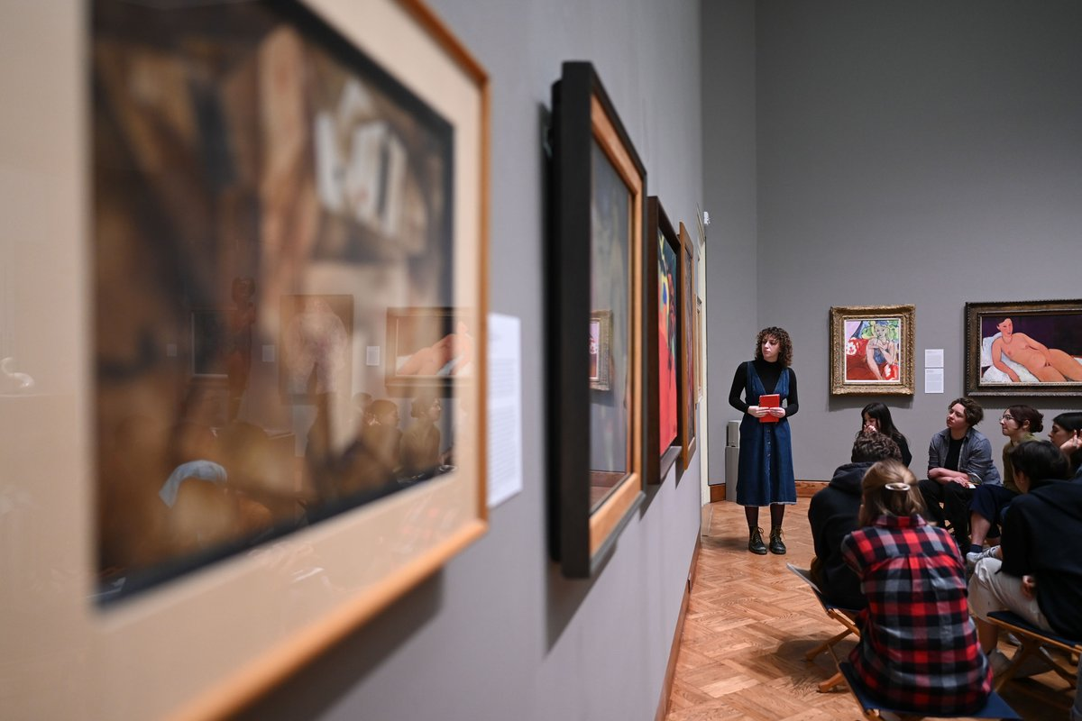 Students sit in an art gallery with another student standing in front of them.