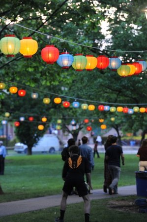 People walk under hanging lanterns