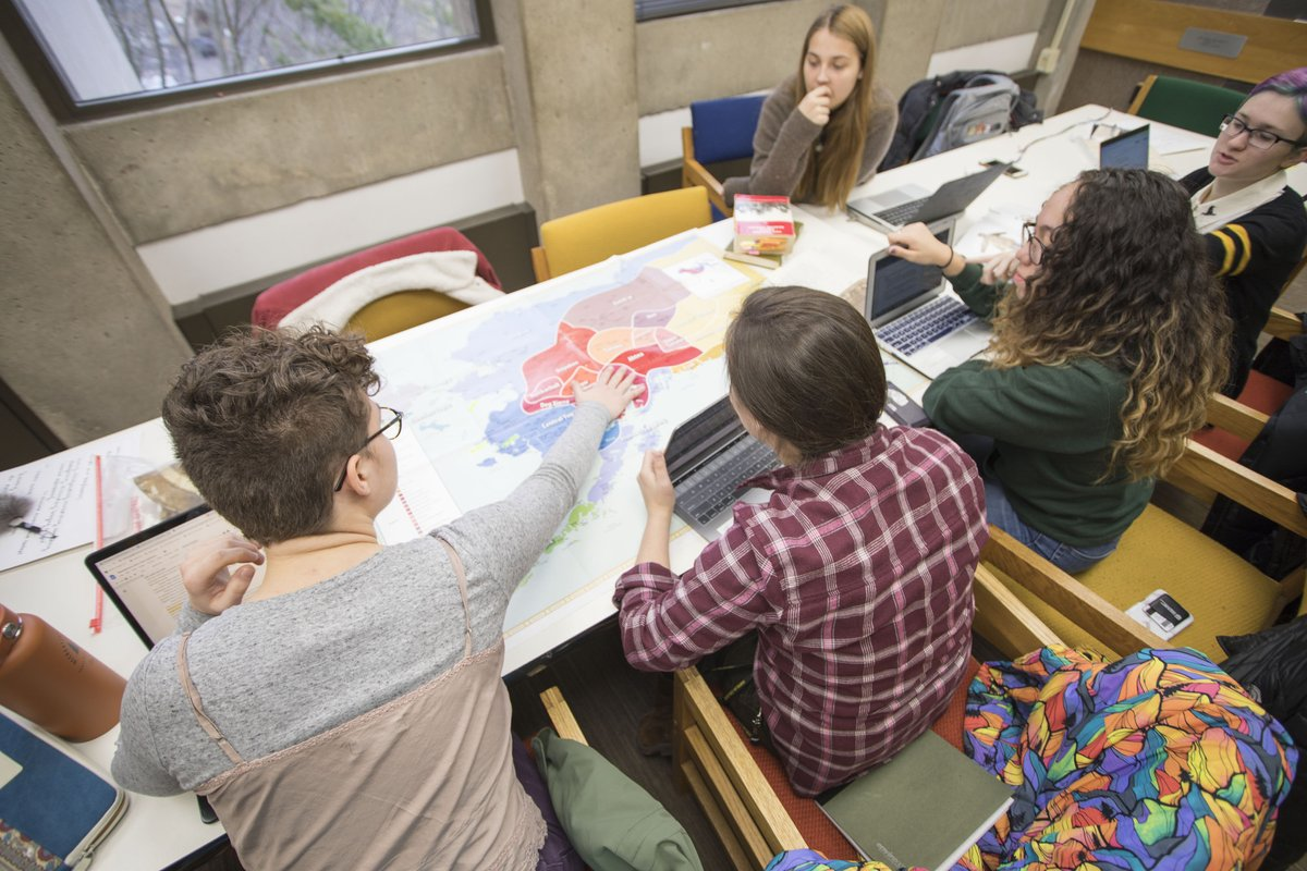 A group of students discuss a map in front of them.